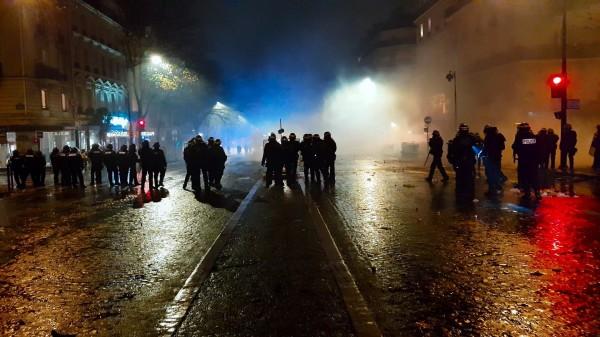 Des policiers en tenue anti-émeute font face à des manifestants dans une rue parisienne
